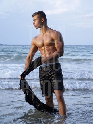 boy with a dreamy look takes off his shirt at sea