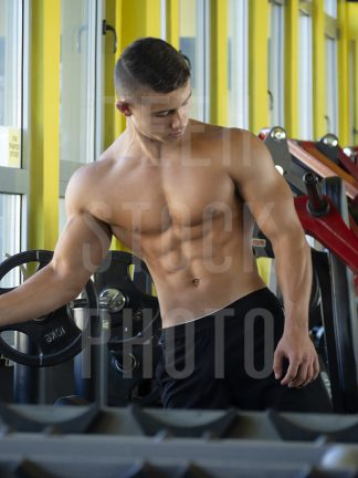 Bodybuilder with a perfect abs and chest is in the gym