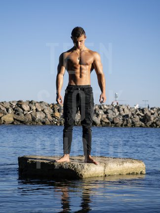Boy with a muscular body stands upright in the water