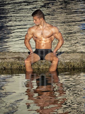 Boy with muscles and a beautiful body is sitting in the water